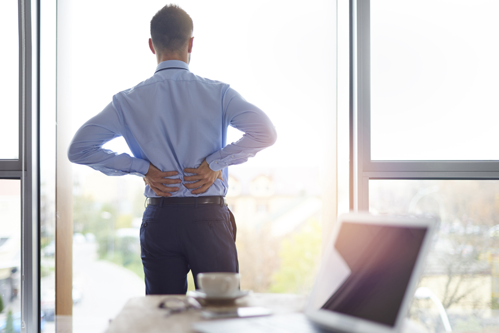 Man in an office with back pain